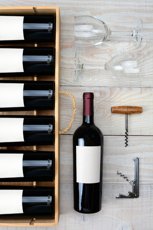 high angle shot: High angle shot of a case of red wine bottles next to a single bottle two wineglasses and cork screws on a rustic white wood table. Vertical format. Stock Photo