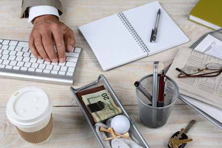 Closeup of a businessmans desk. The white rustic wood desk has a keyboard, coffee cup, keys, notebook, glasses, pencil cup, newspaper money and golf ball and tees, High angle shot with the mans hand on the keyboard. photo