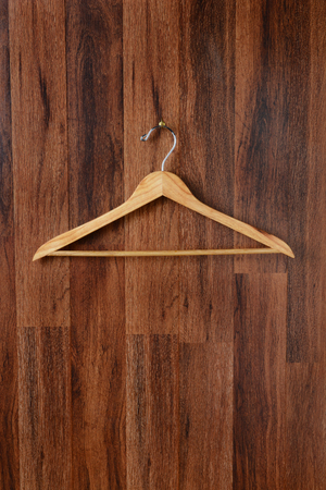 CLOTHES HANGING: Closeup of an empty wooden hanger hanging from a hook on a dark wood paneled wall. Vertical format. Stock Photo