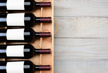 コピー スペースを持つ素朴な白い木製のテーブルに空白のラベルと赤ワインのボトルのケースの高角度のショット。水平方向のフォーマットです。