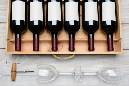 case: Overhead shot of a case of red wine bottles with blank labels  on a rustic white wood table with wine glasses and cork screw below. Horizontal format.
