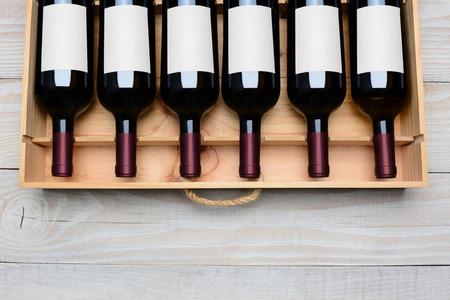 바닥에 복사본 공간 소박한 흰색 나무 테이블에 빈 레이블이있는 레드 와인 병의 경우 오버 헤드 샷. 가로 형식입니다. 스톡 콘텐츠