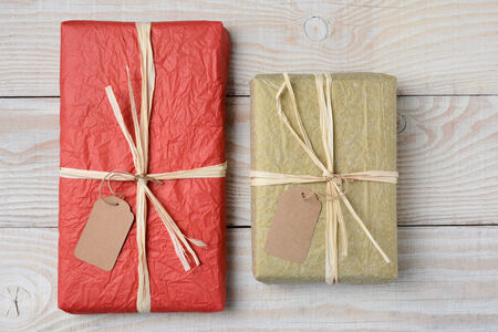 high angle shot: High angle shot of two presents on a white wood rustic table. Wrapped in crumpled tissue paper with blank gift tags. Horizontal format.