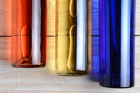 white zinfandel: High angle shot of  red, white, and blue wine bottles on a rustic white wood table. The bottles have no labels. Horizontal format. Stock Photo