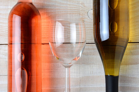 Closeup of a wine glass between a bottle of red wine and a bottle of white wine. All three objects are laying on a rustic white wood table. Horizontal format from a high angle. photo