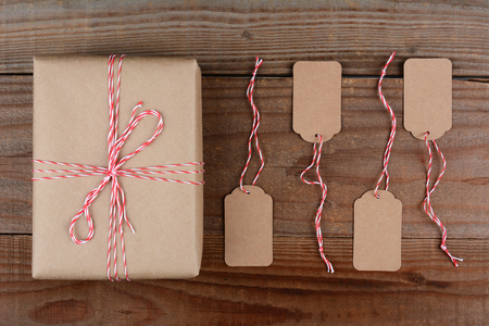 christmas tag: Overhead shot of a Christmas Package wrapped in plain brown paper and tie with red and white string. Four blank tags are next to the gift on a dark rustic wood table.