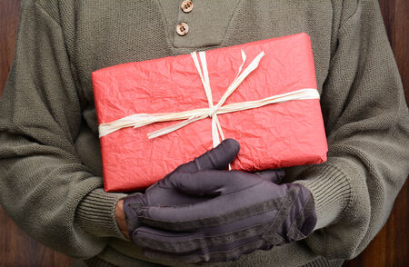 Closeup of a man wearing a sweater and gloves holding a wrapped Christmas present in front of his torso. Man is unrecognizable. Horizontal format. Banque d'images