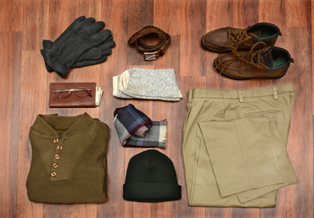 brown clothes: High angle shot of mens winter clothes laid out on a dark wood floor.