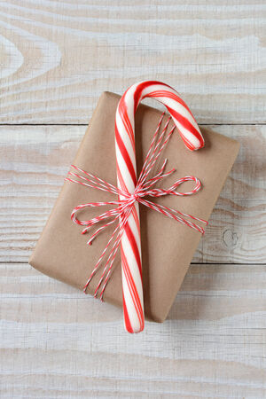 high angle shot: High angle shot of a large candy cane on a small plain brown paper wrapped Christmas present. Vertical format on a rustic white wooden table. Stock Photo