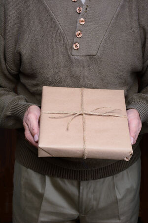 khakis: Closeup of a man holding a parcel in front of his torso. Man is unrecognizable, showing torso only. Vertical format. Stock Photo