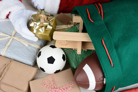 Closeup of Santa Claus filling his bag with toys and presents. Only Santas hands are visible. Wrapped presents soccer ball, football, toy airplane and gifts fill the frame. Horizontal format. photo