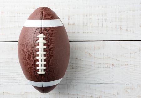 Close-up overhead schot van een Amerikaanse collegiale stijl van voetbal op een witte houten tafel. De bal wordt ot gecompenseerd links met kopie ruimte aan de linkerkant van het beeld.