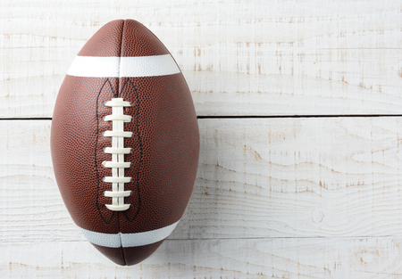 Closeup overhead shot of an American collegiate style football on a whitewashed wood table. The ball is offset ot the left with copy space on the left side of the image. Stock Photo