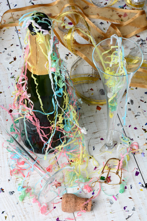 after party: High angle shot of a Champagne bottle, streamers and confetti after a New Years Eve Party. Vertical format with shallow depth of field. Focus is on the foreground and table top. Stock Photo