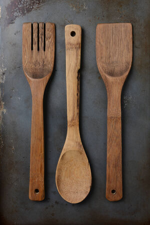 high angle shot: High angle shot of three wood kitchen utensils on an old and well used baking sheet. Vertical format.