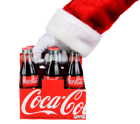 6 pack: IRVINE, CA - DECEMBER 12, 2014: Santa Claus holding a 6 pack of Coca-Cola Classic bottles. Coca-Cola is the one of the worlds favorite carbonated beverages. Editorial