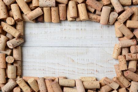 Overhead shot van een groep van wijnkurken vorming van een frame op een rustieke witte houten tafel. Horizontale formaat.