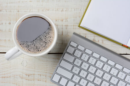 telecommute: Overhead shot of a fresh brewed cup of coffee, an open book and a computer keyboard on a rustic white wood desk. Horizontal format. Stock Photo