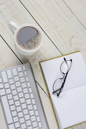 Vertical overhead shot of a home office desk with a cup of coffee, and open book with glasses, and a computer keyboard. The items are on a rustic white washed desk with copy space. Фото со стока