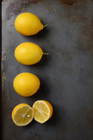 one sheet: High angle shot of a group of lemons, three whole and one cut, on a metal baking sheet. Vertical format.