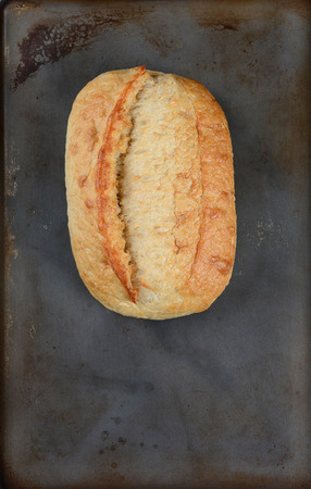 high angle shot: High angle shot of a fresh baked loaf of bread on a baking sheet. Vertical format with copy space.