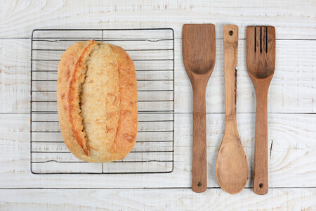 high angle shot: High angle shot of a fresh baked loaf of bread on a cooling rack with wooden spoon, spatual and fork Stock Photo