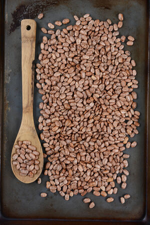 high angle shot: High angle shot of pinto beans and a wooden spoon on a used metal baking sheet
