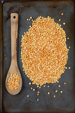 high angle shot: High angle shot of yellow split peas and a wooden spoon on a used metal baking sheet Stock Photo