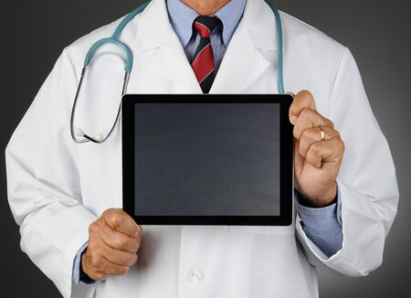 blank tablet: Closeup of a doctor holding a tablet computer with a blank Chalkboard screen in front of his torso.  Horizontal format over a light to dark gray background. Man is unrecognizable.