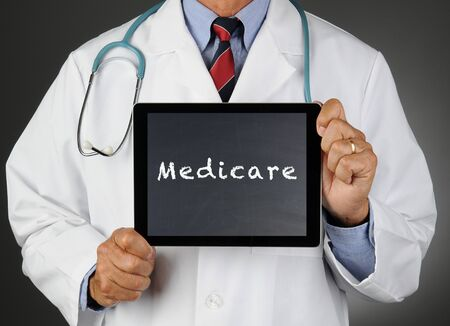 medicare: Closeup of a doctor holding a tablet computer with a chalkboard screen with the word Medicare. Man is unrecognizable. Stock Photo