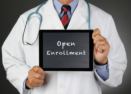 Closeup of a doctor holding a tablet computer with a chalkboard screen with the words Open Enrollment. Man is unrecognizable.