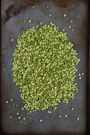 high angle shot: High angle shot of a pile of green split peas on a well used metal baking sheet. Vertical Format. Stock Photo