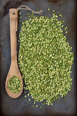 high angle shot: High angle shot of a pile of green split peas and a wooden spoon on a well used metal baking sheet. Vertical Format.