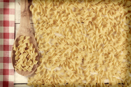 high angle shot: High angle shot of egg noodles, a wooden spoon and checkered tablecloth on a white rustic kitchen table with faded vignette effect applied.