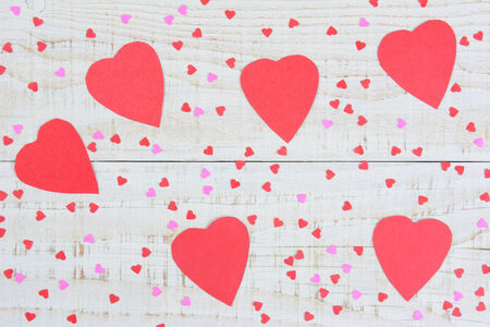 high angle shot: High angle shot of red and pink, large, paper hearts for Valentines Day scattered on a rustic whitewashed wood table. Horizontal format.