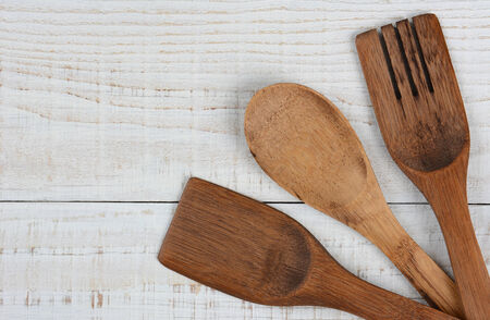 high angle shot: High angle shot of three wooden kitchen utensils in the lower right corner of the frame. The spoon, fork, and spatula have their handles crossed and run out of the image leaving copy space. Stock Photo