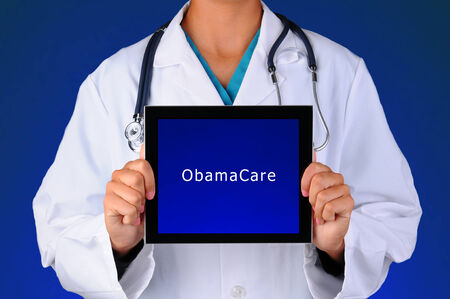 Closeup of a female medical professional holding a tablet computer with a blue screen with the words ObamaCare. Person is unrecognizable on a blue light to dark background.