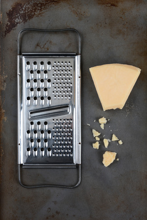 high angle shot: High angle shot of a broken wedge of Parmesan cheese and grater on used baking sheet. Vertical format. Stock Photo