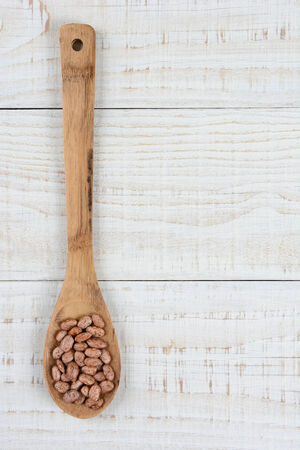 HIgh angle shot of a wooden spoon full of uncooked pinto beans. Vertical format on a rustic white wood kitchen table. photo