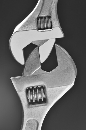 Closeup of two adjustable wrenches locked together over a light to dark gray background. photo