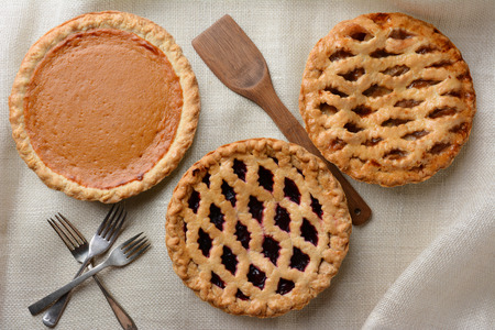 High angle shot of three fresh baked homemade pies, Apple, Cherry and Pumpkin on a burlap table cloth. Horizontal format with forks and wooden spatula. Imagens