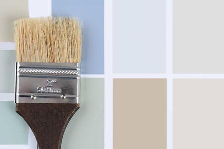 Overhead schot van een penseel met een bruin handvat tot op een blad van kleurstalen. Horizontale indeling met kopie ruimte.