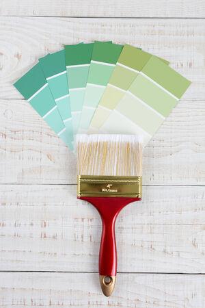 Overhead verticale shot van een penseel en tinten groen kleurstalen op een rustieke witte houten oppervlak. Stockfoto
