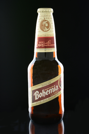 international beer: IRVINE, CA - JANUARY 12, 2015: A bottle of Bohemia beer on a black . From Cerveceria Cuauhtemoc-Moctezuma, founded in 1890, now a subsidiary of Heineken International.