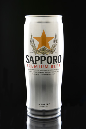 sapporo: IRVINE, CA - JANUARY 12, 2015: A can of Sapporo Beer on a black . The Japanese brewery was founded in 1876 by German trained brewer Seibei Nakagawa. It is the oldest beer brand in Japan.