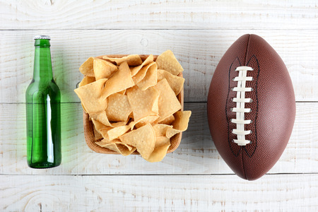 table surface: Beer bottle, bowl of chips and an American style football on a rustic whitewashed wood surface. Horizontal format. The bottle is without label. Stock Photo
