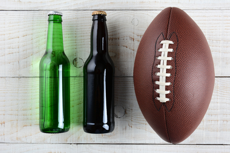 super bowl: Two beer bottles and an American style football on a rustic whitewashed wood surface. Horizontal format. One green bottle and one brown, both without labels.