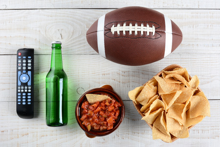 TV Remote, beer bottle, bowl of chips with salsa and an American style football on a rustic whitewashed wood surface. Horizontal format. Great for Super Bowl party themed projects.