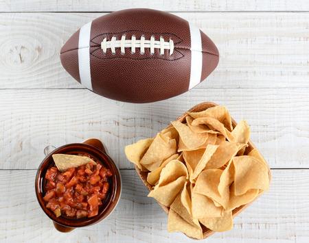 Haute angle de tir d'un bol de chips un pot plein de salsa fraîche de maïs et un ballon de football américain sur une table en bois rustique blanchie à la chaux. Format horizontal. Banque d'images - 35329370