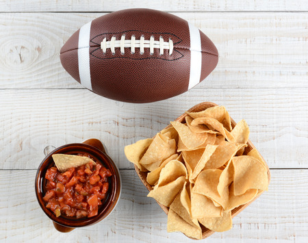 High angle shot of a bowl of corn chips a crock full of fresh salsa and an American football on a whitewashed rustic wood table. Horizontal format.